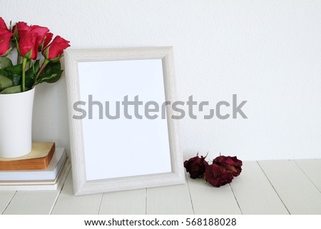 mock up white frame photo with red roses on wooden table