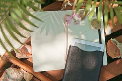Mock up with electronic book and notebook diary, outdoor summer photo with palm shadows