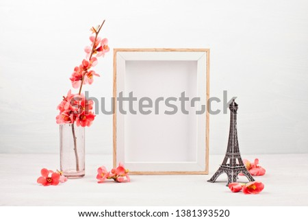 Mock up with empty picture frame, decorative Effel tower and pink tender spring flowers.