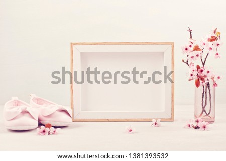 Mock up with empty picture frame, pink tender spring flowers and small baby girl shoes. Baby shower, girl birthday concept