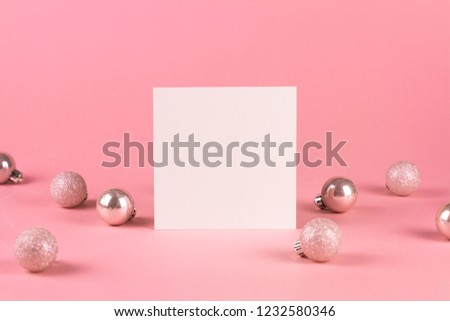 Mock up with square invitation card on trendy pastel light pink background with christmas ornaments. Greeting card and silver Christmas baubles. Minimal christmas concept.