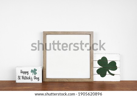 Mock up wood frame with St Patricks Day decor on a wood shelf. Shabby chic wood signs. Square frame against a white wall. Copy space.