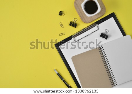 Mock up workspace with blank clip board, office supplies, pen, coffee cup on a wooden stand and eyeglasses on yellow background. Flat lay, top view #1338962135