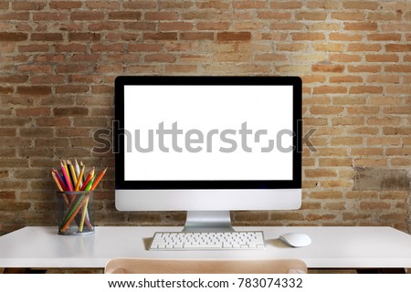 Mock up : Workspace with blank white desktop computer, pencils and stationery items. Blank screen for graphics display montage.