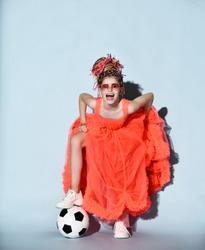 Mocking laughing loud girl with colorful dreadlocks in sneakers stands with soccer ball under foot holding lifting fur hem of her bright coral dress. Girls in football concept
