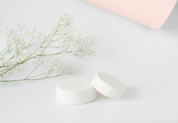 Mockup background for product presentation. Concrete podium and branch with flowers in the background on white.Front view.