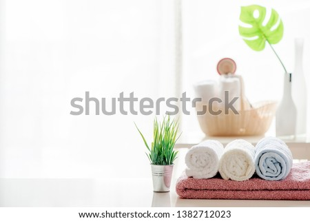 Mockup bath towel on white table with houseplant in white room, copy space for product display.