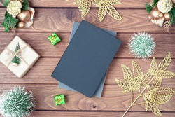 Mockup blank black book cover with Christmas gift box, Xmas ornaments and Christmas tree model decor on wooden table background. Flat lay, Top view with copy space for your Christmas New Year artwork.