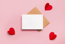 Mockup blank greeting card for valentines day. Composition with red hearts for Valentine's Day on a pale pink background. Flat lay. Love and relationships concept.