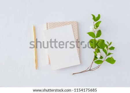 Mockup blank paper card and branch with green leaves on a white background. Flat lay, top view #1154175685
