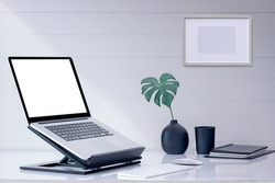 Mockup blank screen laptop computer on wooden stand with keyboard and mouse on white top table.