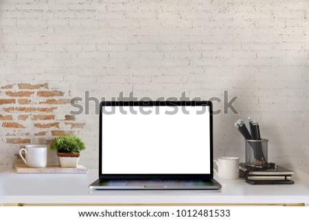 Mockup blank screen laptop on desk. Workspace with laptop and office supplies. #1012481533