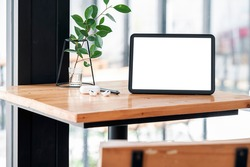 Mockup blank screen tablet and gadget on wooden table.