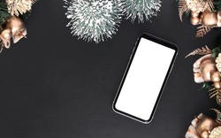 Mockup blank white screen smartphone on black desk table background for Christmas and New Year party background, Flat lay top view with copy space for your Merry Christmas and Happy New year artwork.