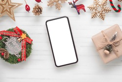 Mockup blank white screen smartphone on white desk background for Christmas and New Year, Flat lay top view with copy space for your Merry Christmas and Happy New year artwork.