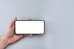 Mockup cell phone. male hand holding phone horizontally with blank white screen. Mockup phone horizontal. human left hand holding black horizontal mobile phone