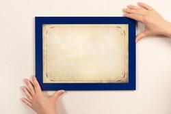 mockup diploma. woman hanging photo frame mockup on wall. OLD grunge certificate with vintage ornamental frame mockup