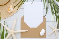 Mockup envelope with card template on white wooden background. Tropical palm leaf, summer hat, seastars and shell. Invitation or greeting card concept