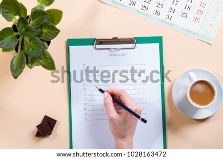 Mockup for check list, empty note paper with pen and coffee cup on light background. Office, writer or study concept. female hand with a pencil