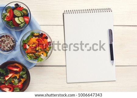 Mockup for healthy dish recipe. Fresh juicy vegetable salads border, blank notepad with copy space and pen on white wooden background, top view. #1006647343