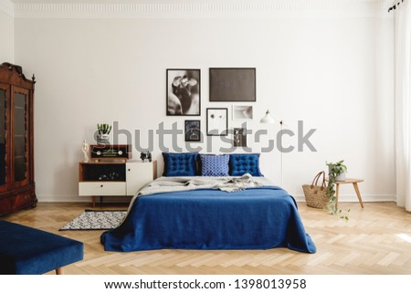 Mockup gallery on the wall of navy blue vintage bedroom in tenement house. Real photo concept
