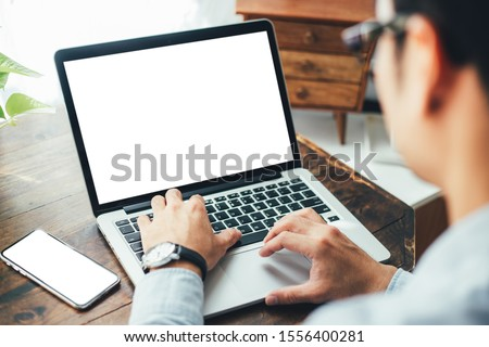 mockup image blank screen computer,cell phone with white background for advertising text,hand man using laptop texting mobile contact business search information on desk in office.marketing and design