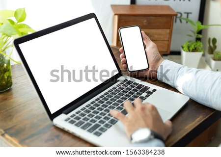 mockup image blank screen computer,cell phone with white background for advertising text,hand man using laptop texting mobile contact business search information on desk in office.marketing and design #1563384238