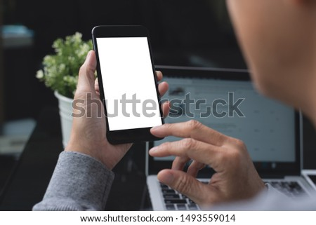 Mockup image, business man hand holding blank screen mobile smart phone, working on laptop computer with digital tablet on table in modern office for website or application design, over shoulder view