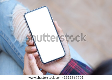 Mockup image man hand holding texting using black mobile,cell phone at desk with copy space,white blank screen for text.concept for contact business,people communication,technology electronic device.  #1311567701