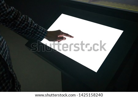Mockup image - man touching white empty interactive touchscreen display kiosk in dark room of modern technology museum. Mock up, template, scifi, education, futuristic and technology concept #1425158240