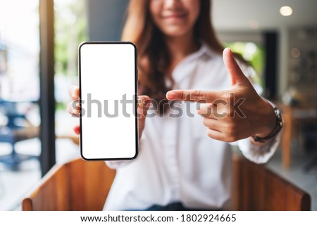Mockup image of a beautiful woman pointing finger at a mobile phone with blank white screen  Foto stock ©