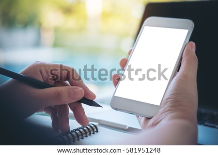 Mockup image of a hand holding and showing smart phone with blank white screen by swimming pool