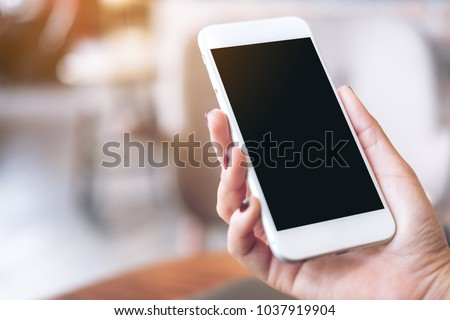 Mockup image of a hand holding white mobile phone with blank black desktop screen with blur background #1037919904