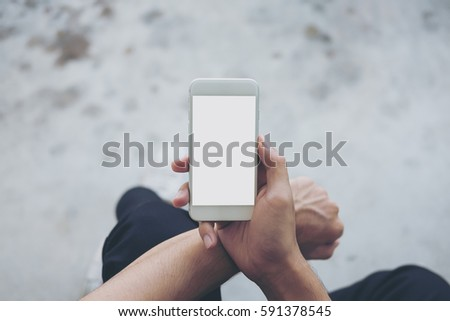 Mockup image of a man sitting on the street and holding white mobile phone with blank white screen