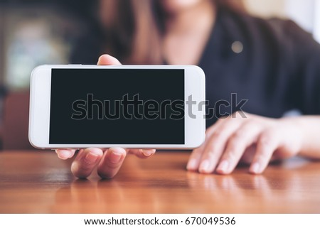 Mockup image of a woman holding and showing white horizontal mobile phone with blank black screen in restaurant