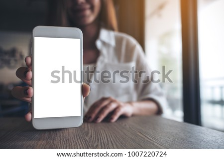 Mockup image of a woman holding and showing white mobile phone with blank screen on the table in modern cafe
