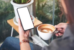 Mockup image of a woman holding and using black mobile phone with blank desktop screen while drinking coffee in cafe