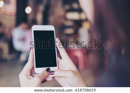 Mockup image of a woman holding mobile phone with blank black screen in modern loft cafe