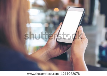 Mockup image of a woman holding white mobile phone with blank desktop screen with blur background #1211092078