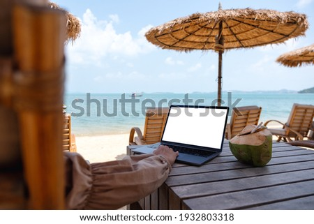 Mockup image of a woman using and touching on laptop touchpad with blank desktop screen while sitting on the beach Stock fotó ©