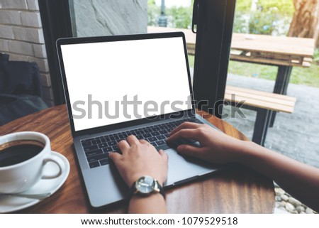 Mockup image of a woman using and typing on laptop with blank white desktop screen on wooden table in cafe #1079529518