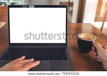 Mockup image of a woman using laptop with blank white screen while drinking coffee on wooden table in office