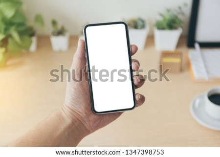 mockup image of cell phone white blank screen for text.Businessman at workplace Think business investment plan.Contact Investor using mobile,computer.make note appointment information in the notebook #1347398753