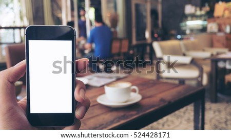 Mockup image of hand holding black mobile phone with blank white screen and hot latte coffee on vintage wood table in cafe #524428171