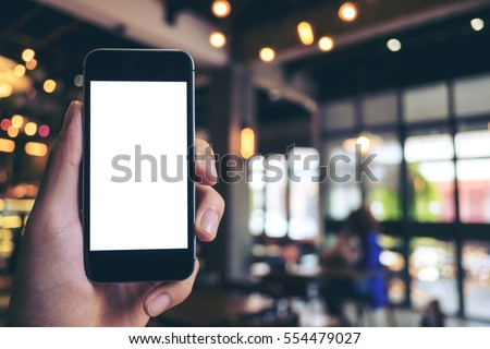 Mockup image of hand holding black mobile phone with blank white screen in cafe #554479027