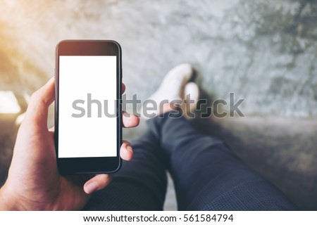Mockup image of hand holding black mobile phone with blank white screen  with white canvas shoes on concrete polishing wall
