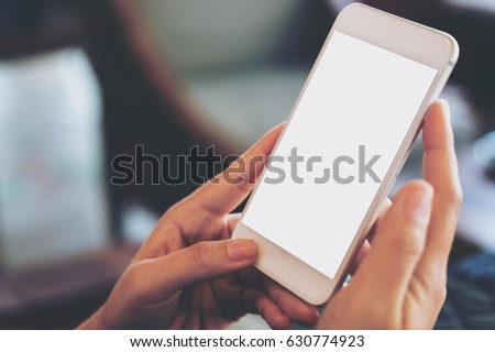 Mockup image of hand holding mobile phone with blank white screen in vintage cafe #630774923