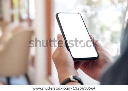 Mockup image of hands holding black mobile phone with blank desktop screen in cafe