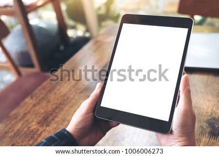 Mockup image of hands holding black tablet pc with blank desktop white screen on wooden table in cafe background