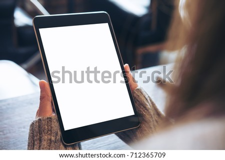 Mockup image of hands holding black tablet pc with blank white screen on wooden table in cafe